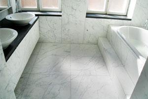 Badrum i vit marmor från Carrara med svart granitbänk