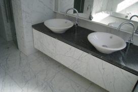 Badrum med golv i marmor och marmormöbelmed granitbänk